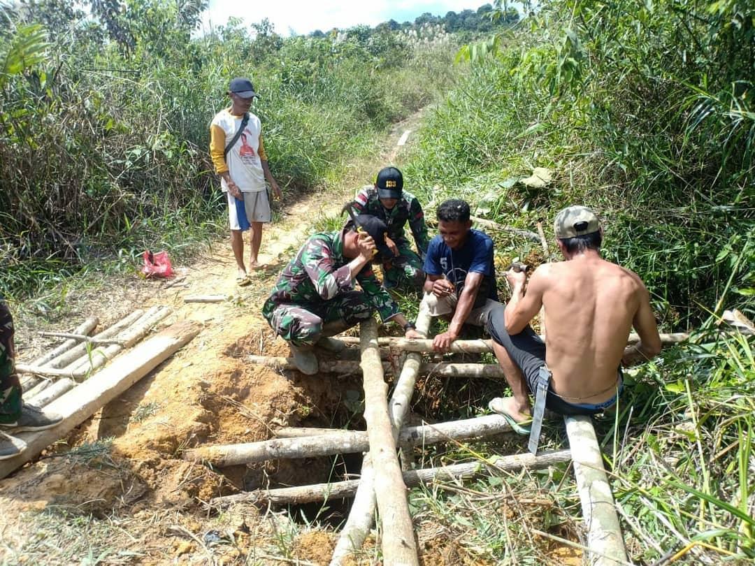 Gotong royong tersebut dipimpin oleh Serda Dega, bahu membahu bersama warga memperbaiki jembatan yang rusak (pendamXII/tpr)