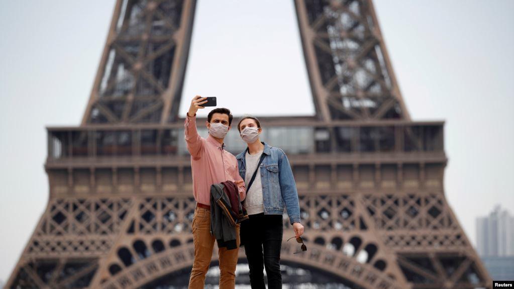 Pengunjung mengenakan masker wajah melakukan selfie di alun-alun Trocadero dekat Menara Eiffel, di Paris, saat Perancis mulai secara bertahap mengakhiri lockdown secara nasional di tengah pandemi Covid-19, 16 Mei 2020.